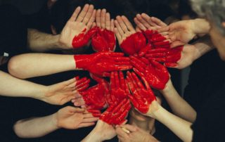 Painted hands forming a heart.
